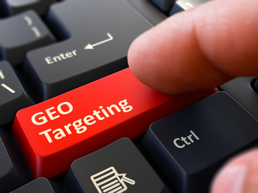 GEO Targeting Red Button - Finger Pushing Button of Black Computer Keyboard. Blurred Background. Closeup View.-1