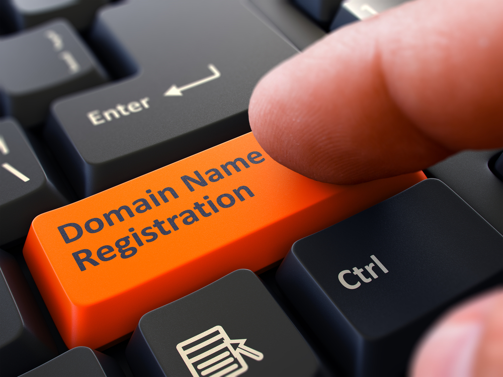 Finger Presses Orange Button  Domain Name Registration on Black Keyboard Background. Closeup View. Selective Focus.